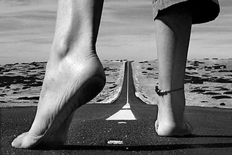 Pies descalzos sobre una larga carretera iniciando la marcha