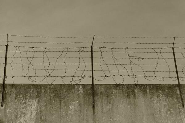Alambre de espinas a lo alto de un muro.